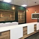 White and wood countertop display in front of grass wall
